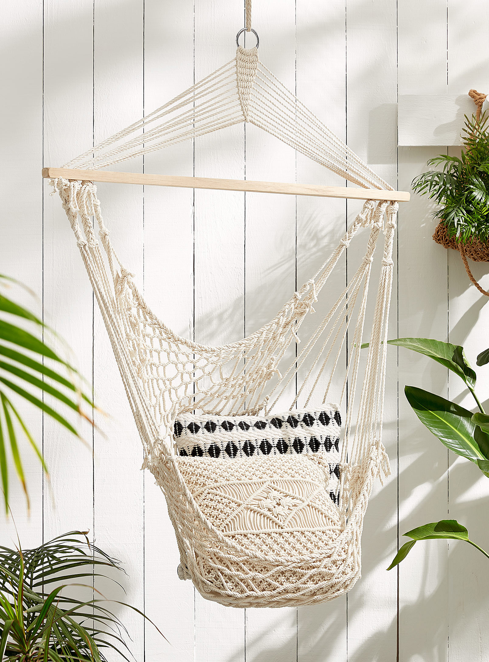 A crocheted chair hangs indoors