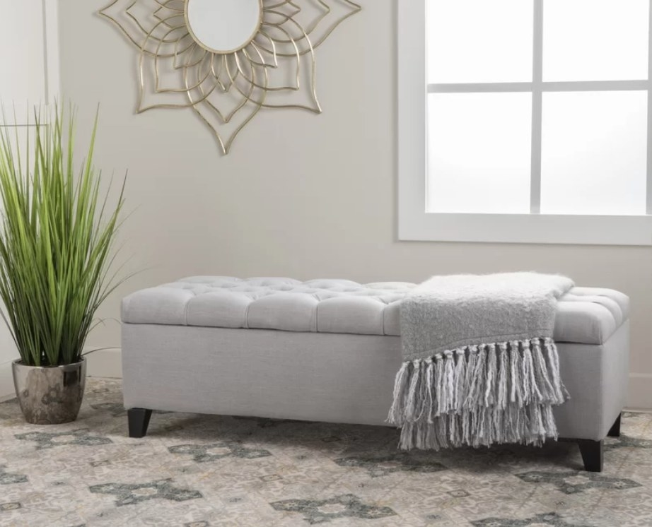 Gray upholstered storage bench with gray throw and dark wood legs