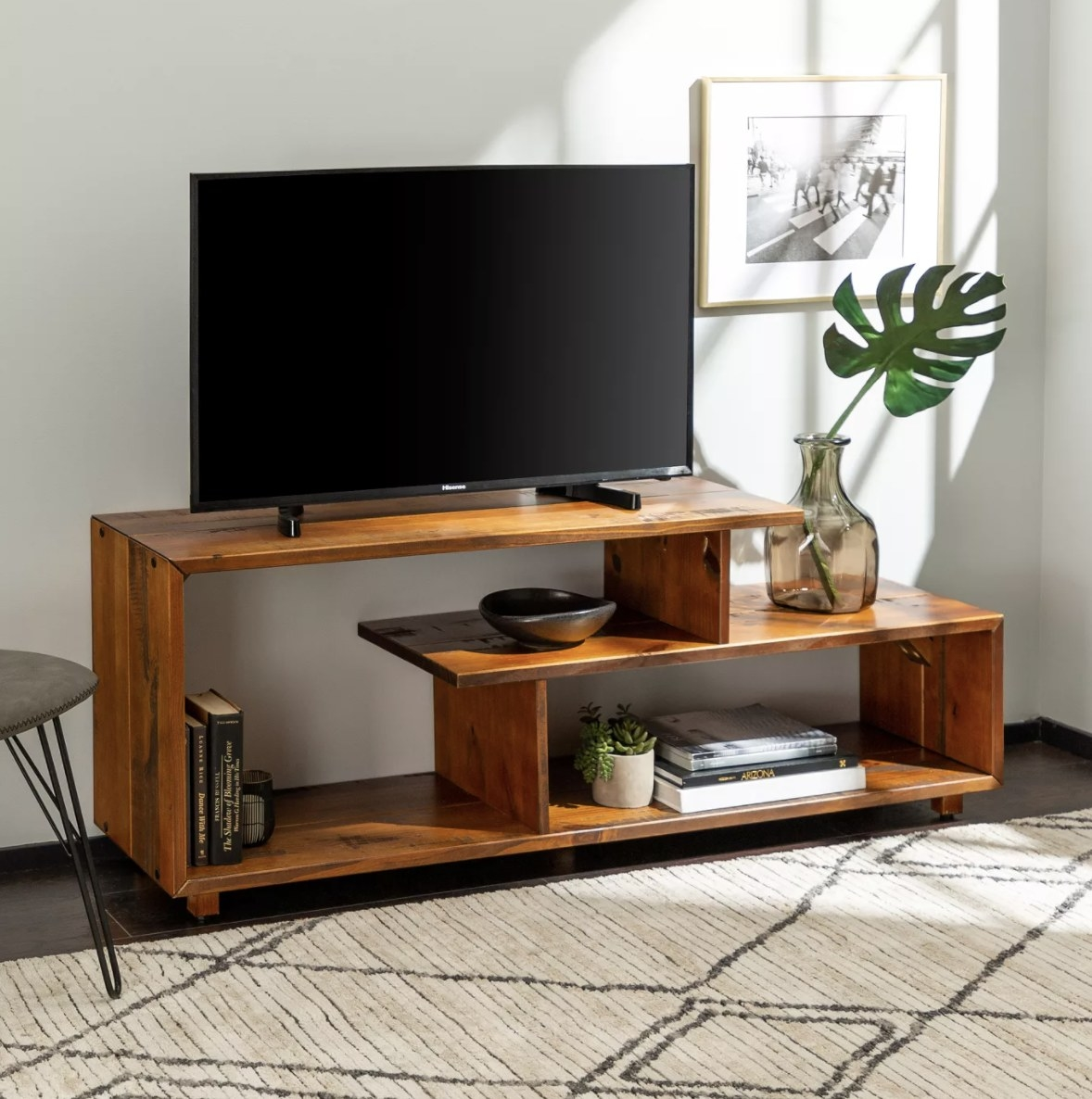 the tv stand with a tv on top of it and books, vases, and plants inside of it on top of a carpet