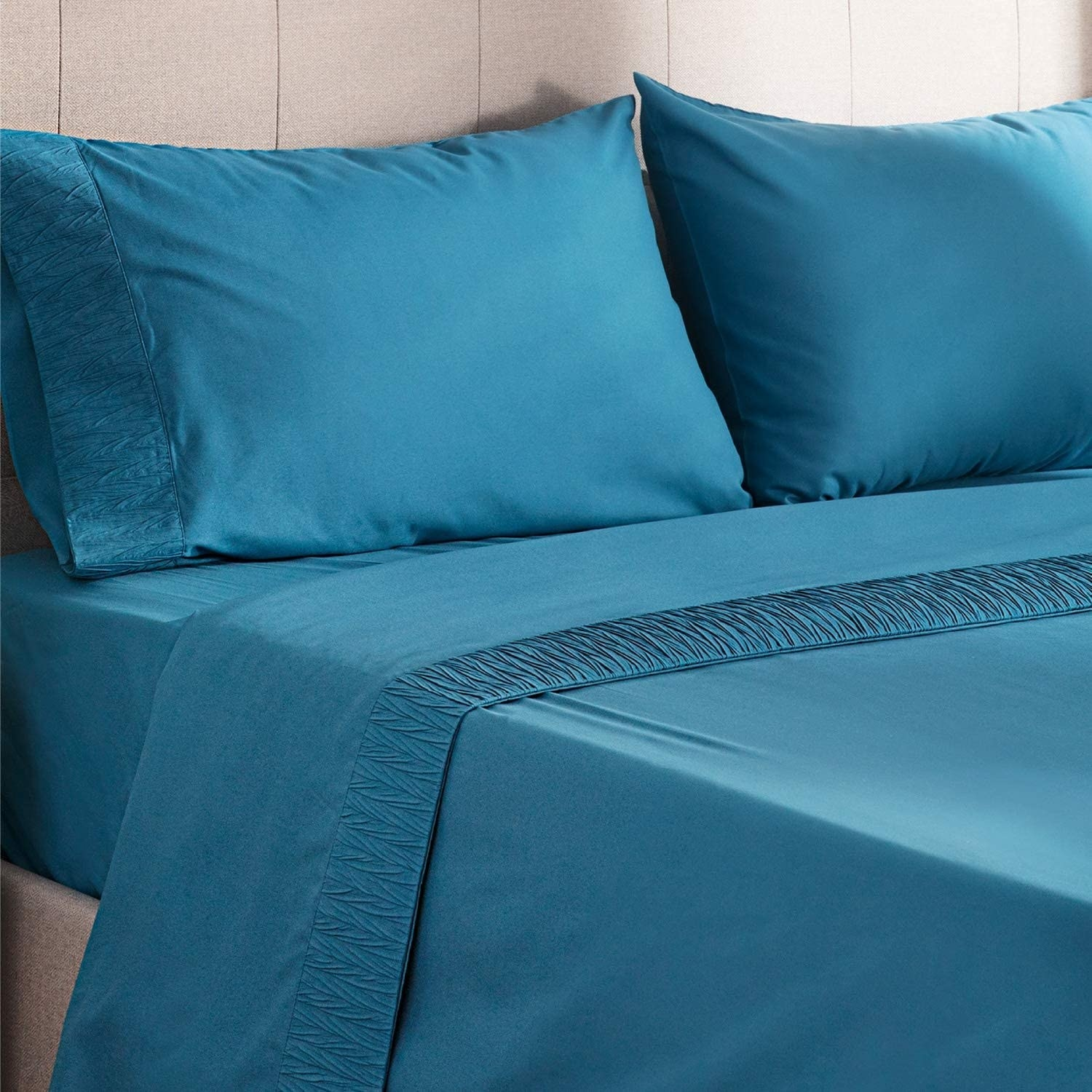 The sheets in teal on a bed