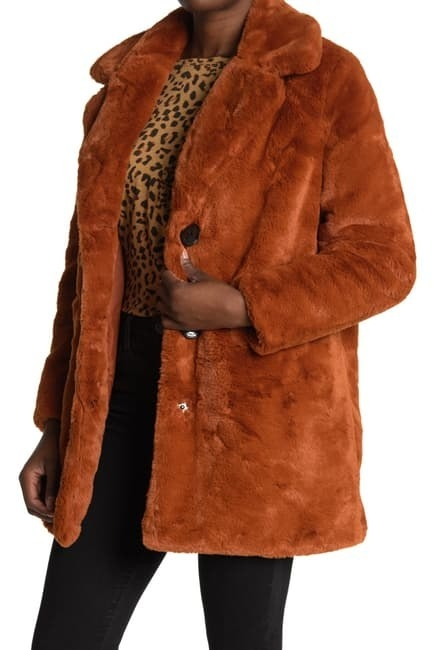 Model wearing the brown fuzzy coat with snap buttons that hits at the upper thigh