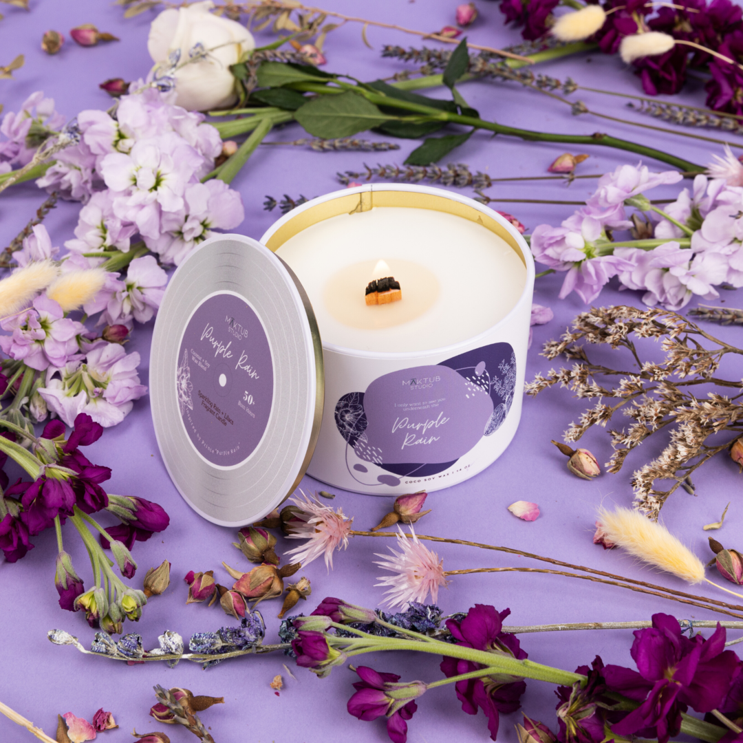 """a white lit candle with """"purple rain"""" in script on the front"""