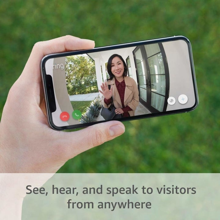 Model holding smartphone showing camera feed of Ring video doorbell