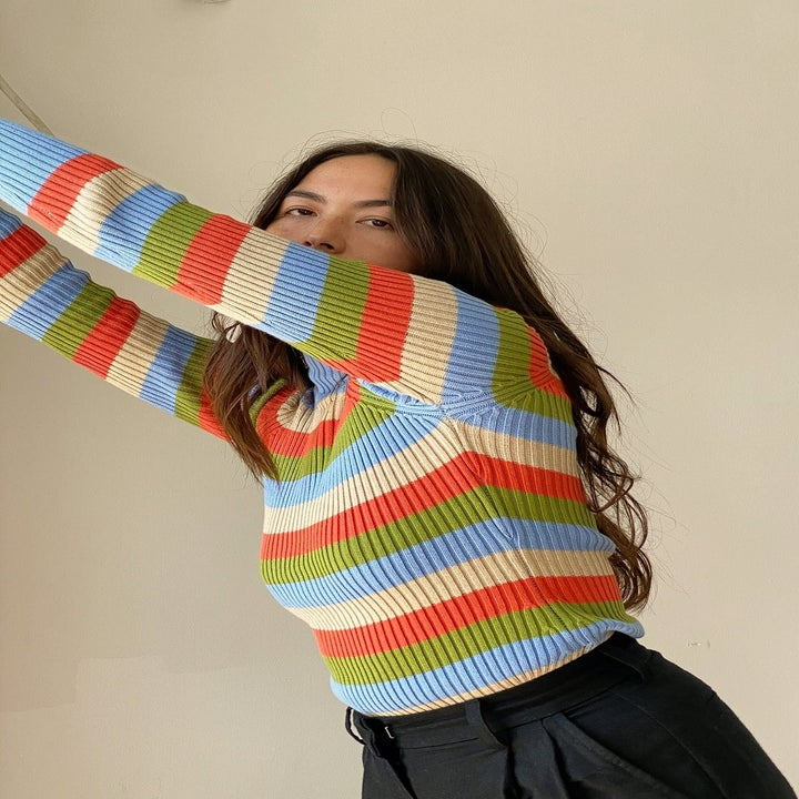 Model wearing blue, red, cream and olive horizontal striped sweater