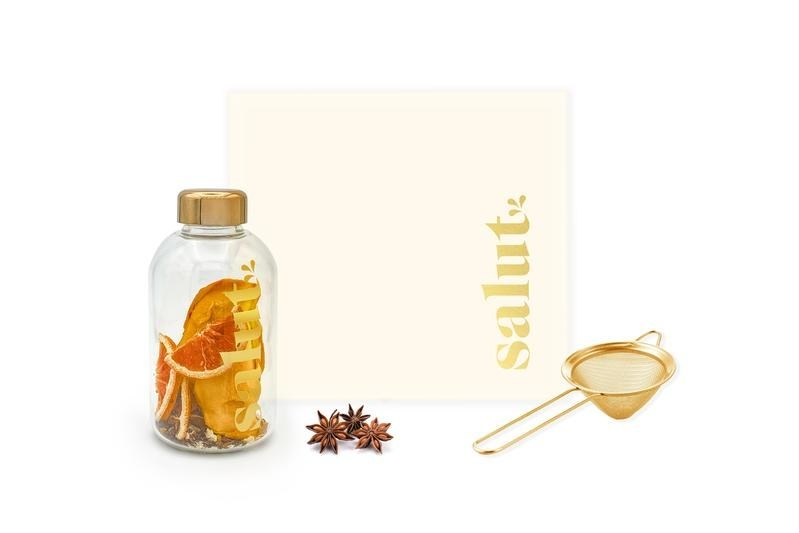 glass bottle filled with anise and dried blood oranges next to a small strainer
