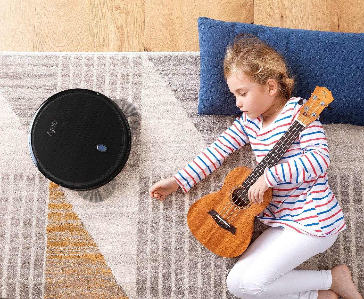 Child holding guitar and sleeping next to Eufy robotic vacuum cleaning the carpet