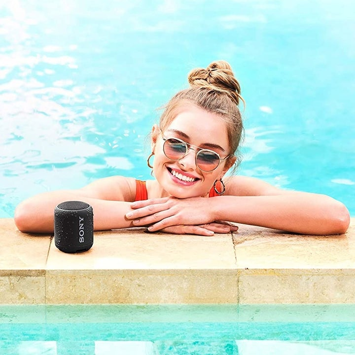 Model posing next to Sony Bluetooth speaker in the pool