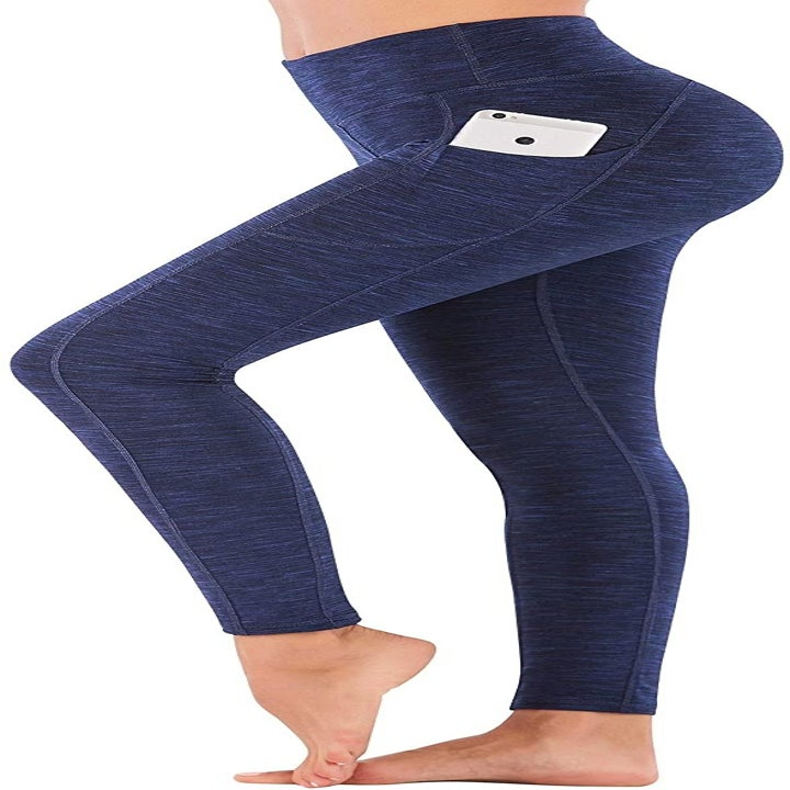 model wearing the leggings in heather navy with a phone in the hip pocket