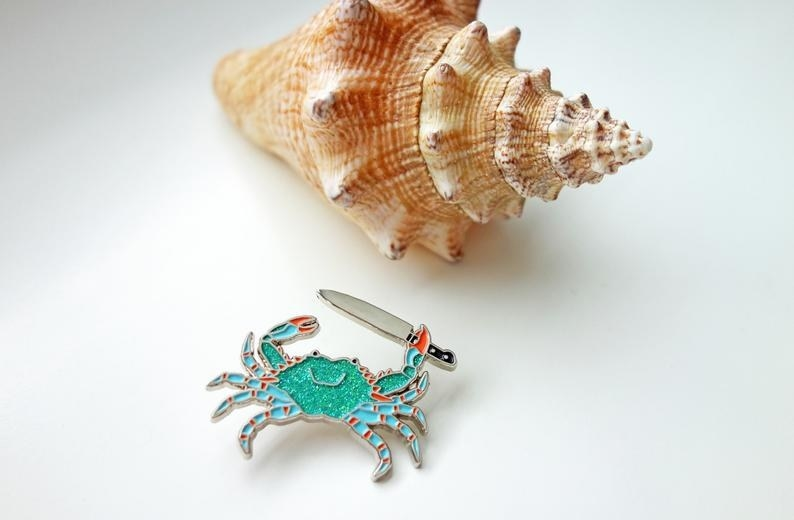 enamel pin of crab holding a knife