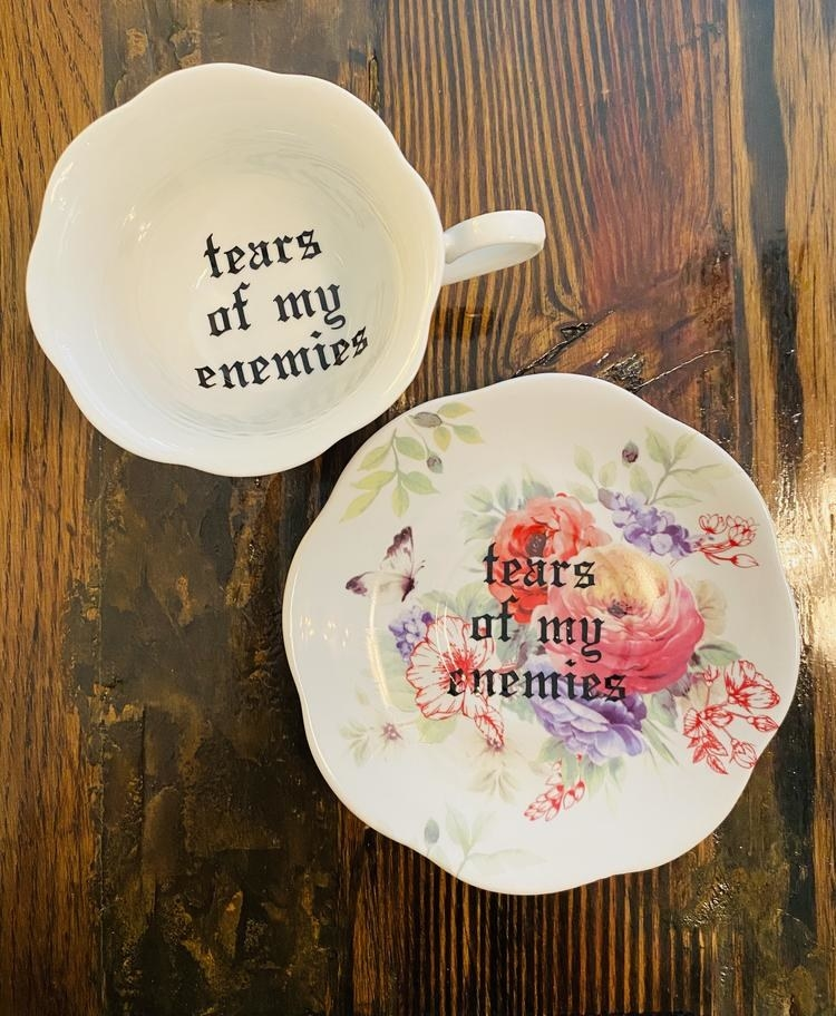"A teacup and saucer with the caption, ""tears of my enemies"""