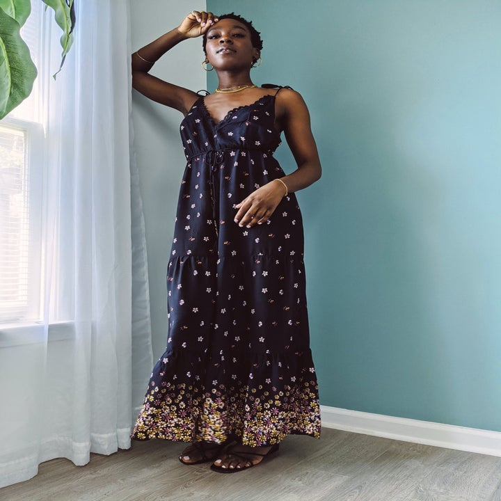 Model wearing a spaghetti strap maxi jumpsuit in blue with flowers all over it