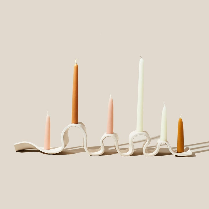 A wavy candelabra with colorful candles in it