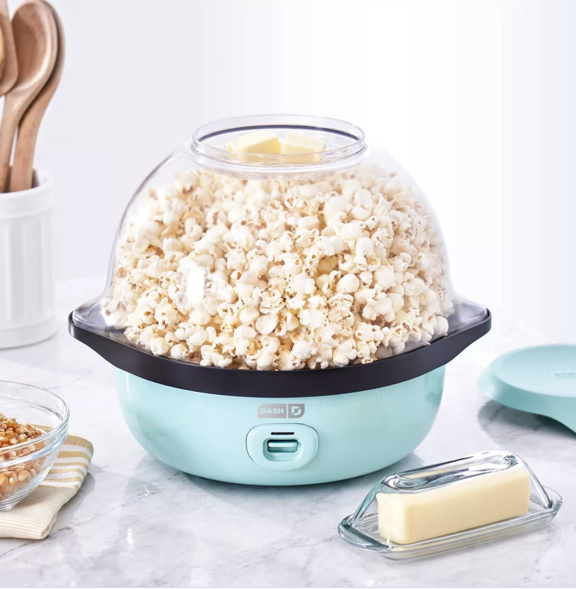 a popcorn maker in blue with popcorn inside of it and a stick of butter and kernels next to it