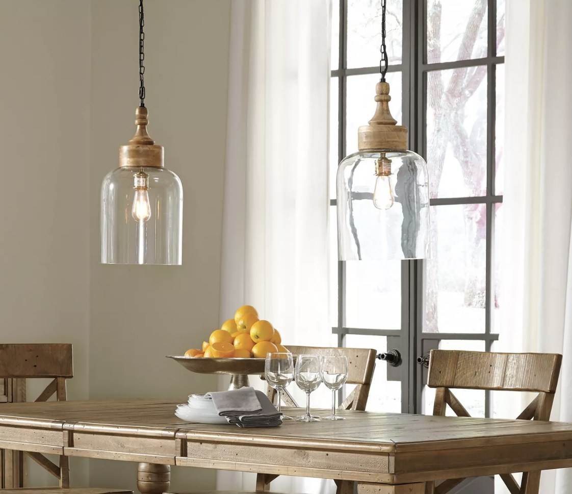 two led pendant lights hanging over a wood table with lemons, napkins, and wine glasses on top of it
