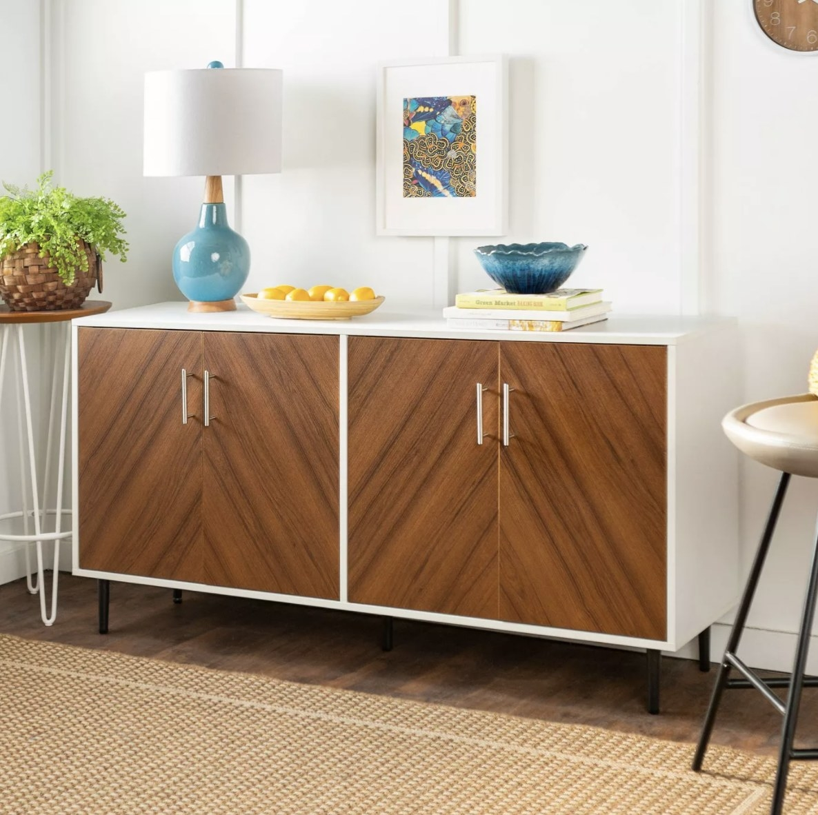 the storage buffet with wood doors, metal handles, and decorations on top of it