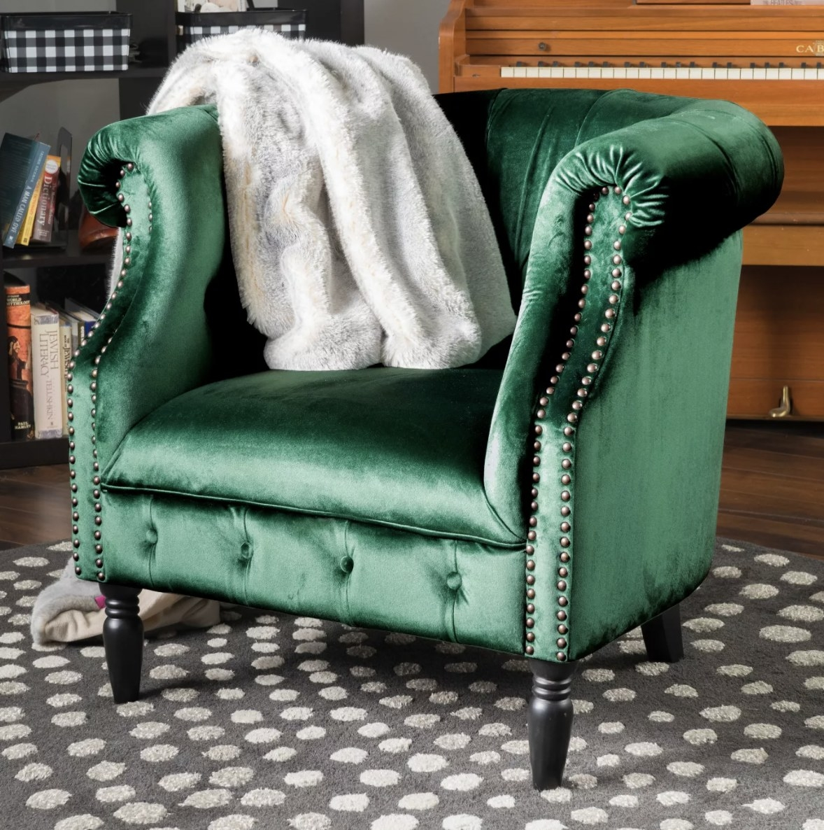 a velvet club chair in green with stud detailing on it and a white throw on top of it