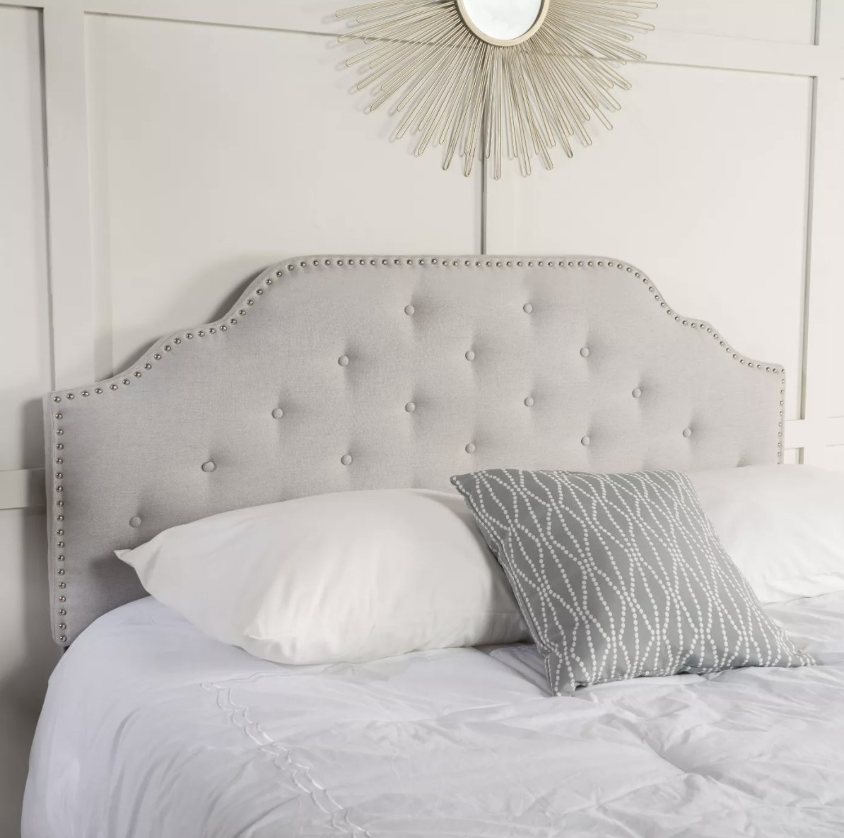 a gray headboard with studded detailing behind a bed with two white pillows, a gray throw pillow, and a white comforter