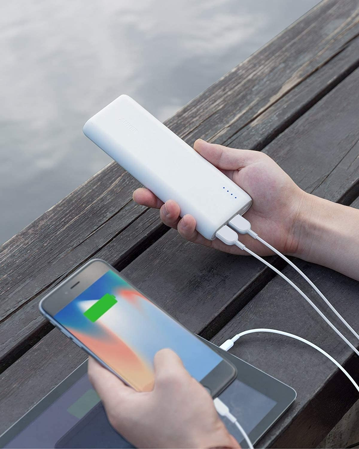 A person holding a slim rectangular power bank charger in their hand