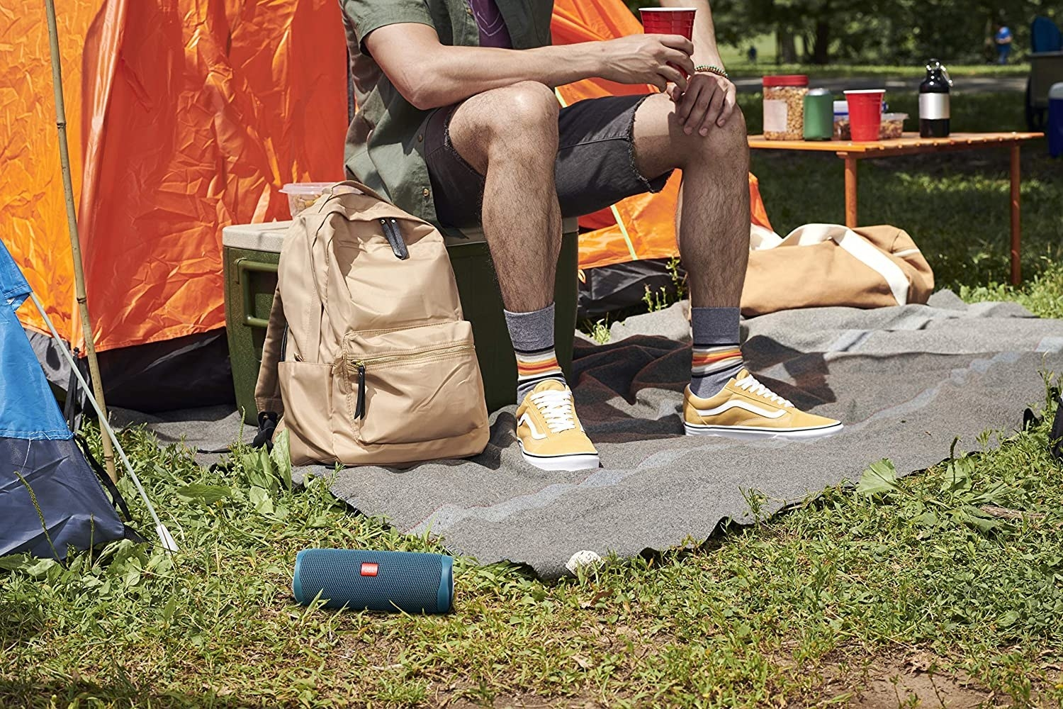 A person sitting on a cooler with a portable speaker on the grass in front of them