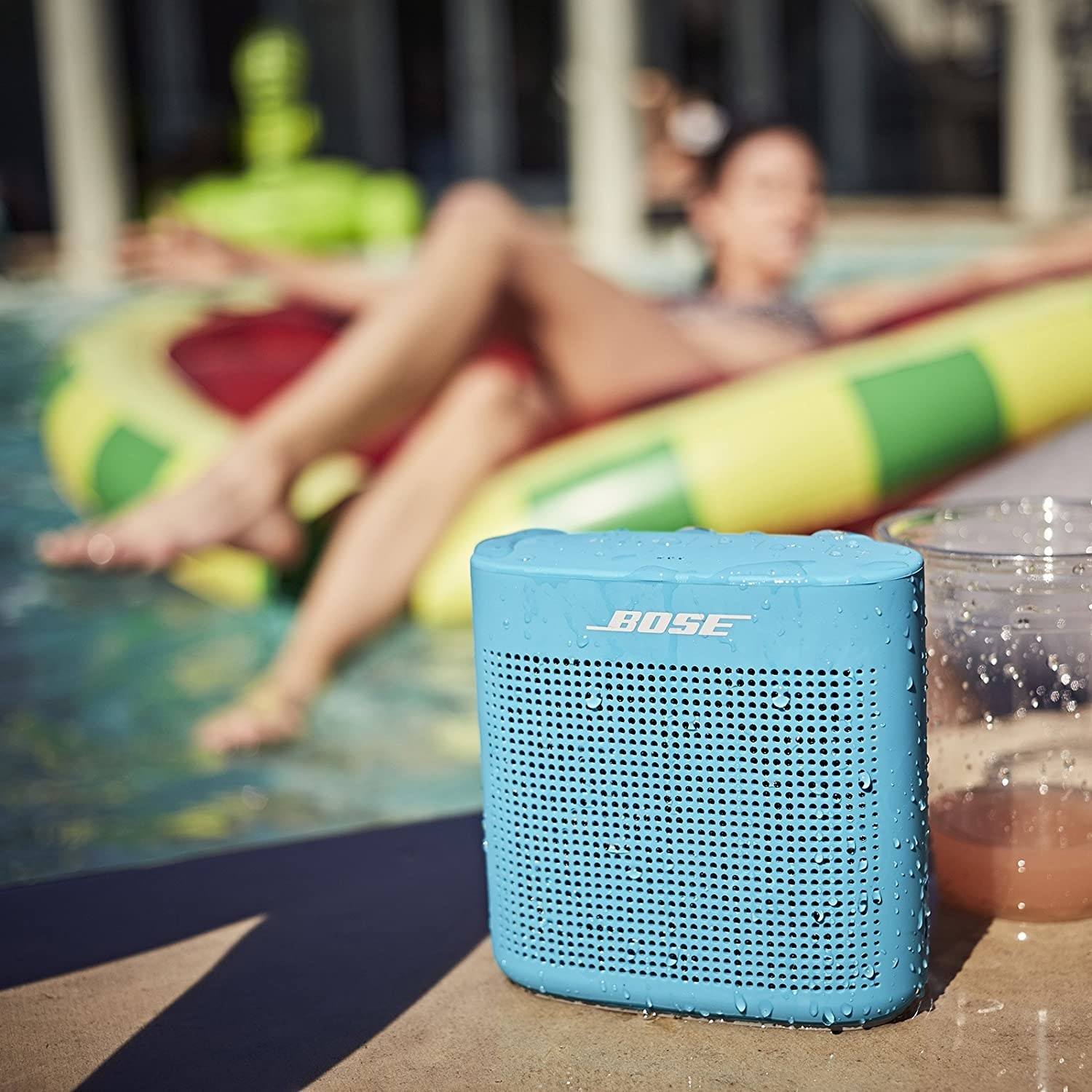 A small Bluetooth speaker on the edge of a pool