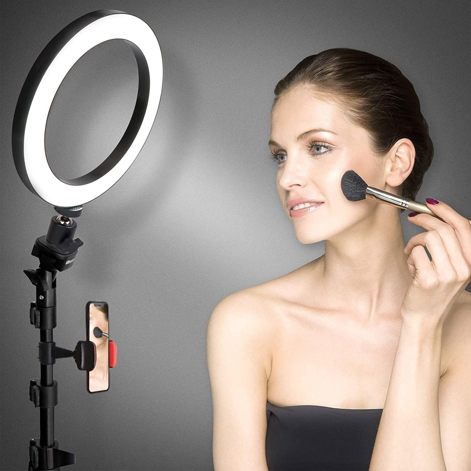 A person sitting in front of a ring light while applying makeup