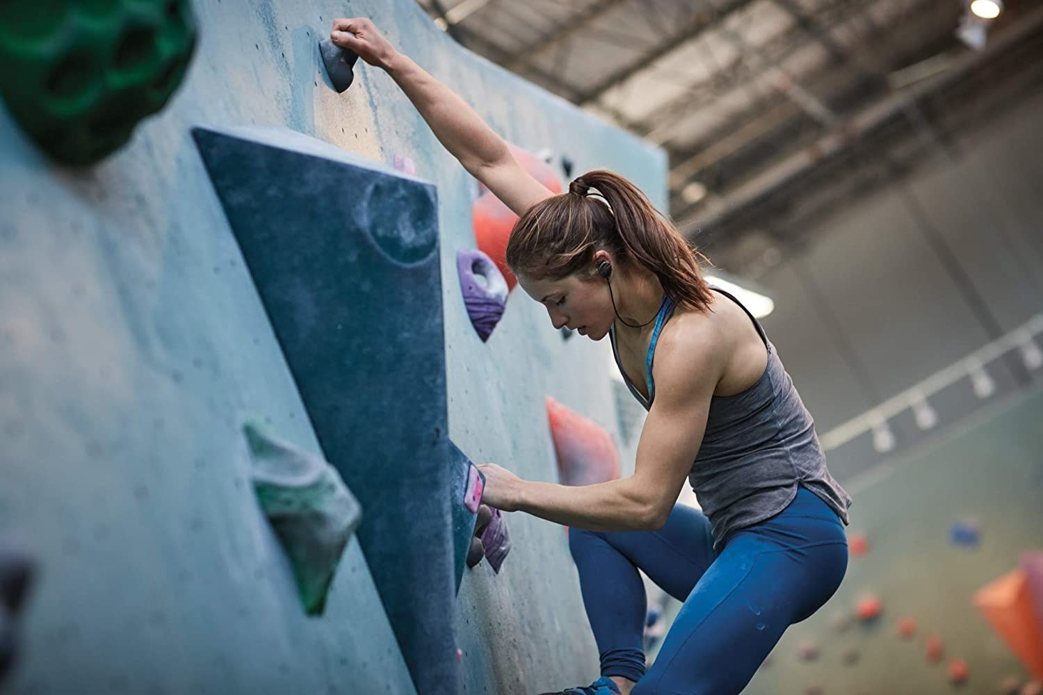 A person rock climbing while wearing headphones