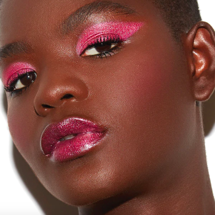 model with deep skin tone waring bright pink eyeshadow look