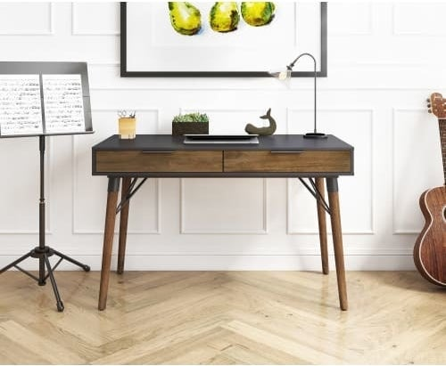 The dark wood writing desk with a black top and two drawers