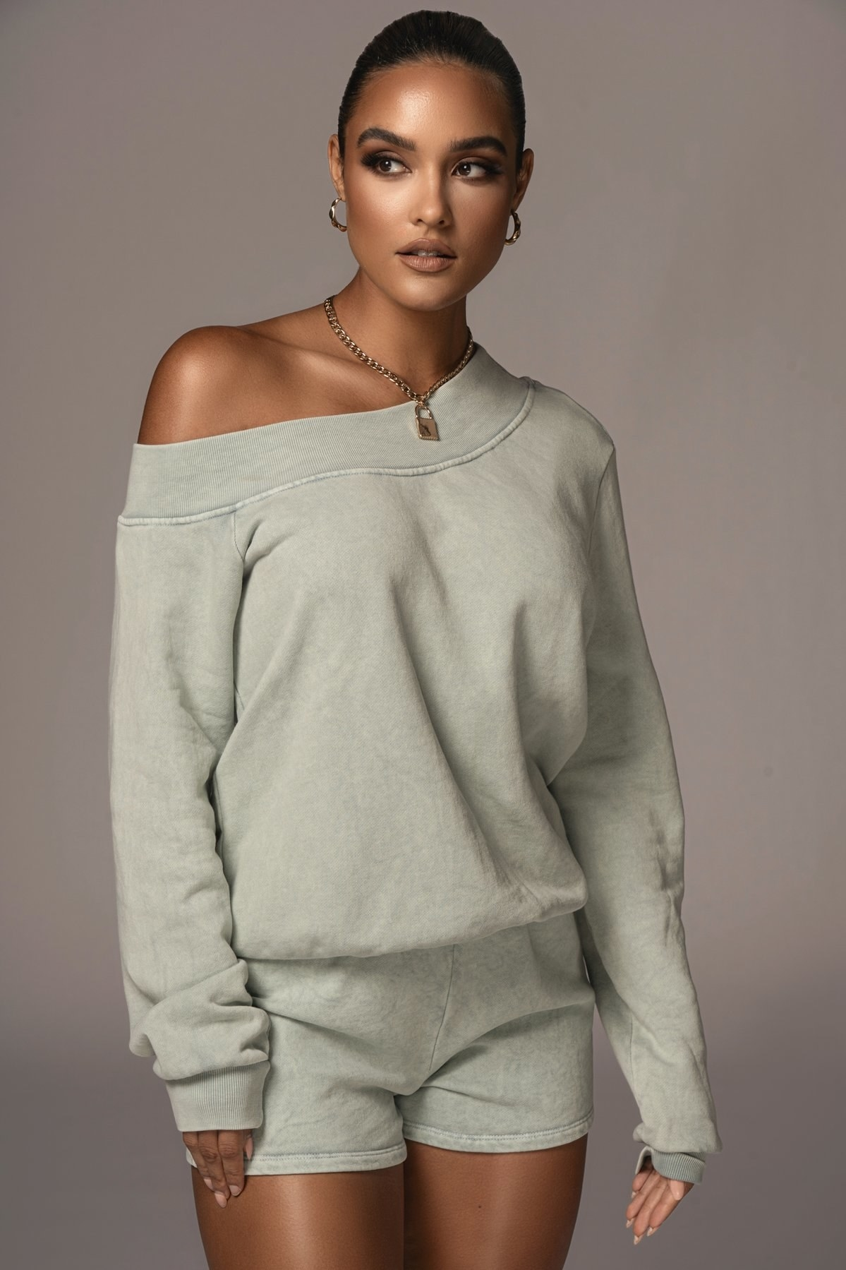 model wearing a sage green off-shoulder sweatshirt and matching shorts