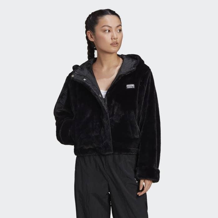 A person wears a faux fur jacket