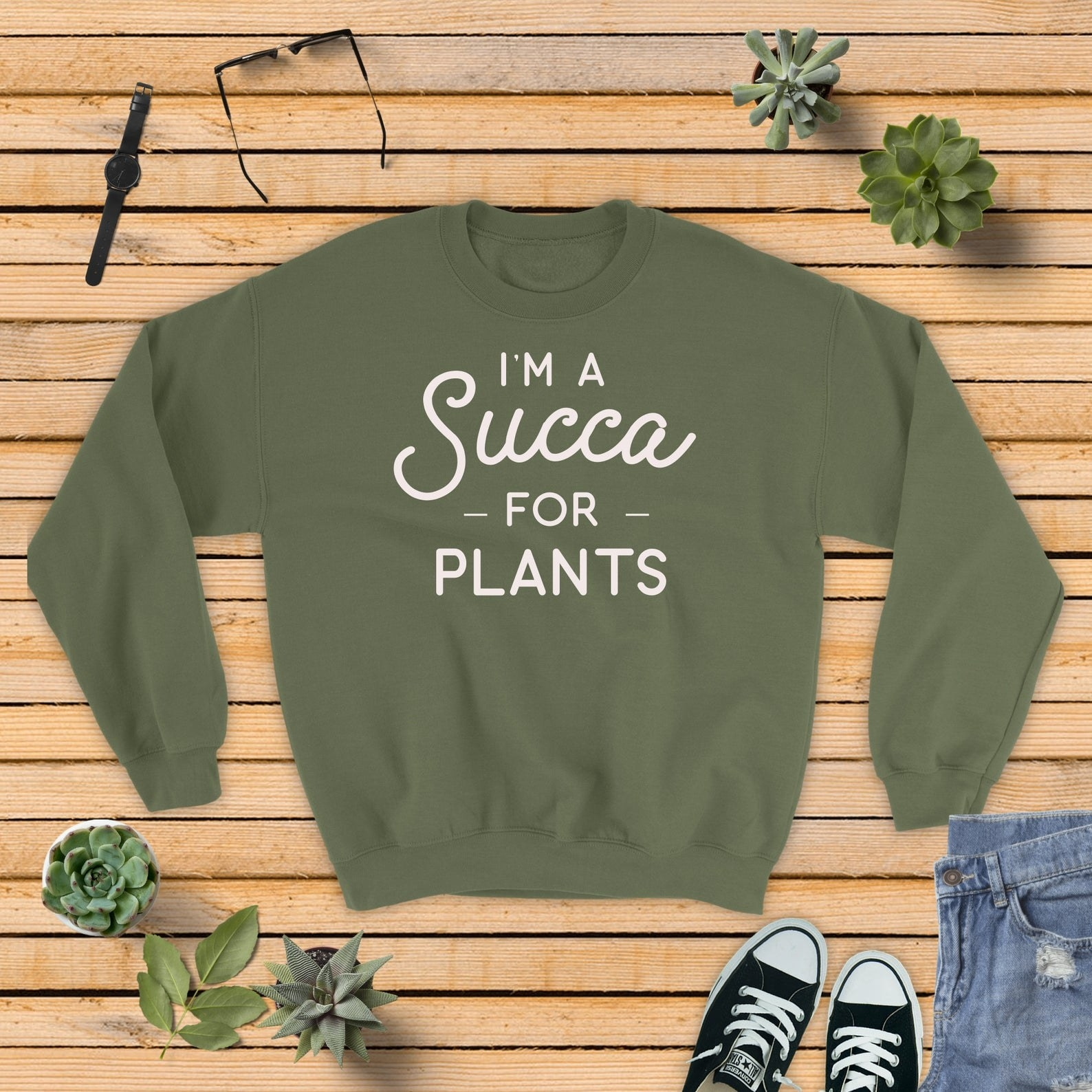 "green sweatshirt that says ""Succa for plants."""