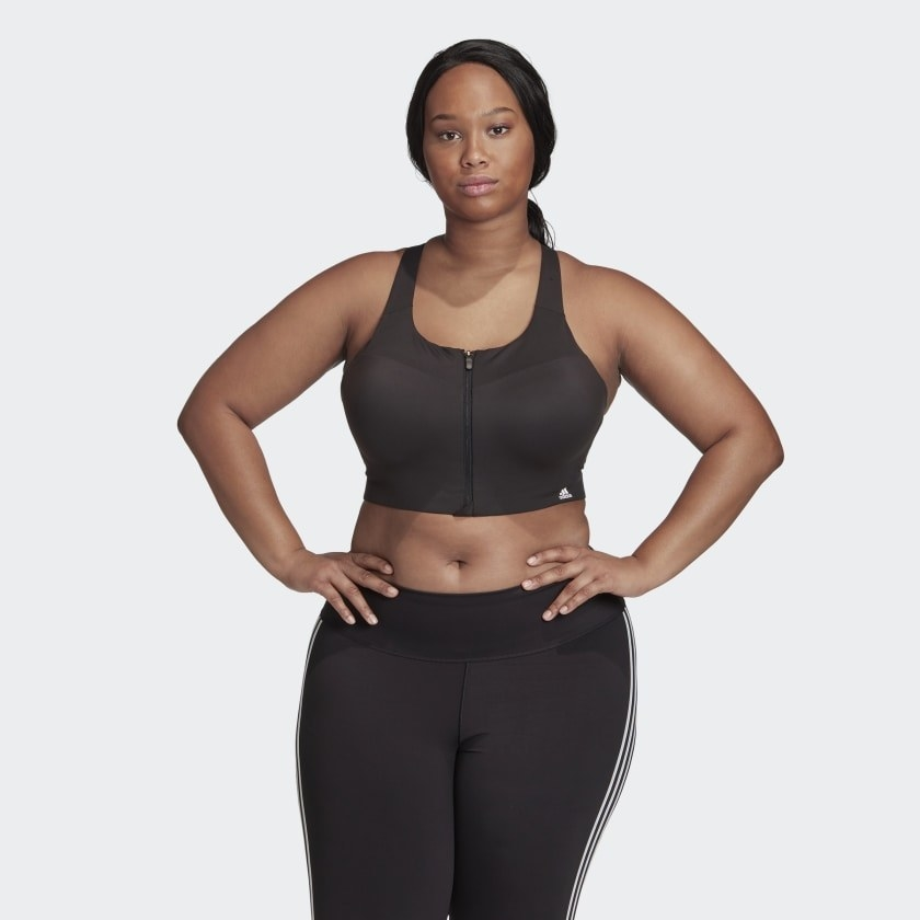 A person wears a full coverage sports bra with a zip at the front