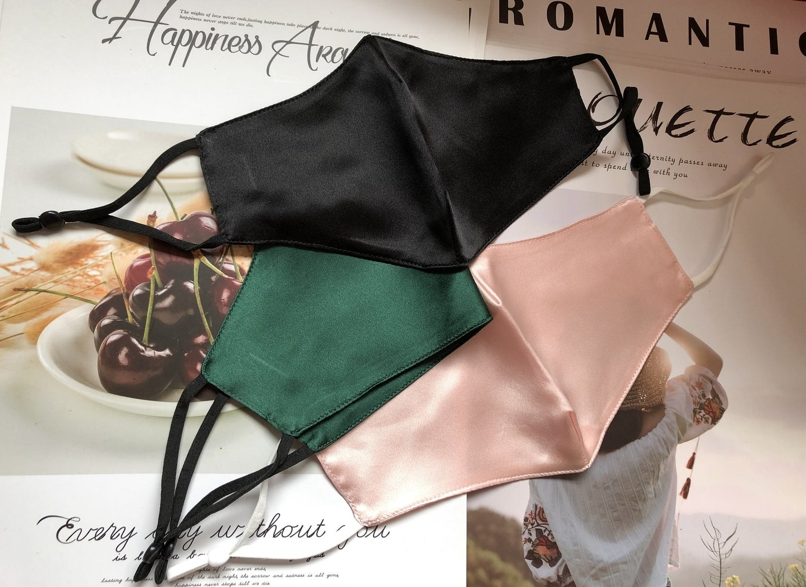 three silk masks in black, emerald green, and pink