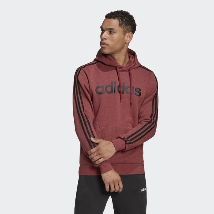 A person wears a hoodie with the Adidas printed on the front and three stripes down each arm