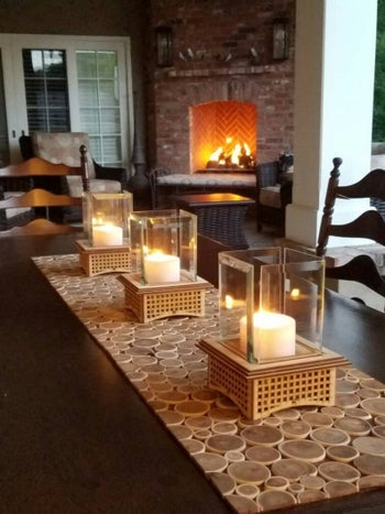 four of the tabletop fireplaces lined on a table runner with candles inside of them lit