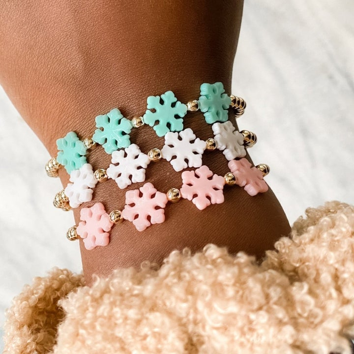 model's arm wearing three bracelet made of snowflakes. They are mint, light pink, and pink respectively