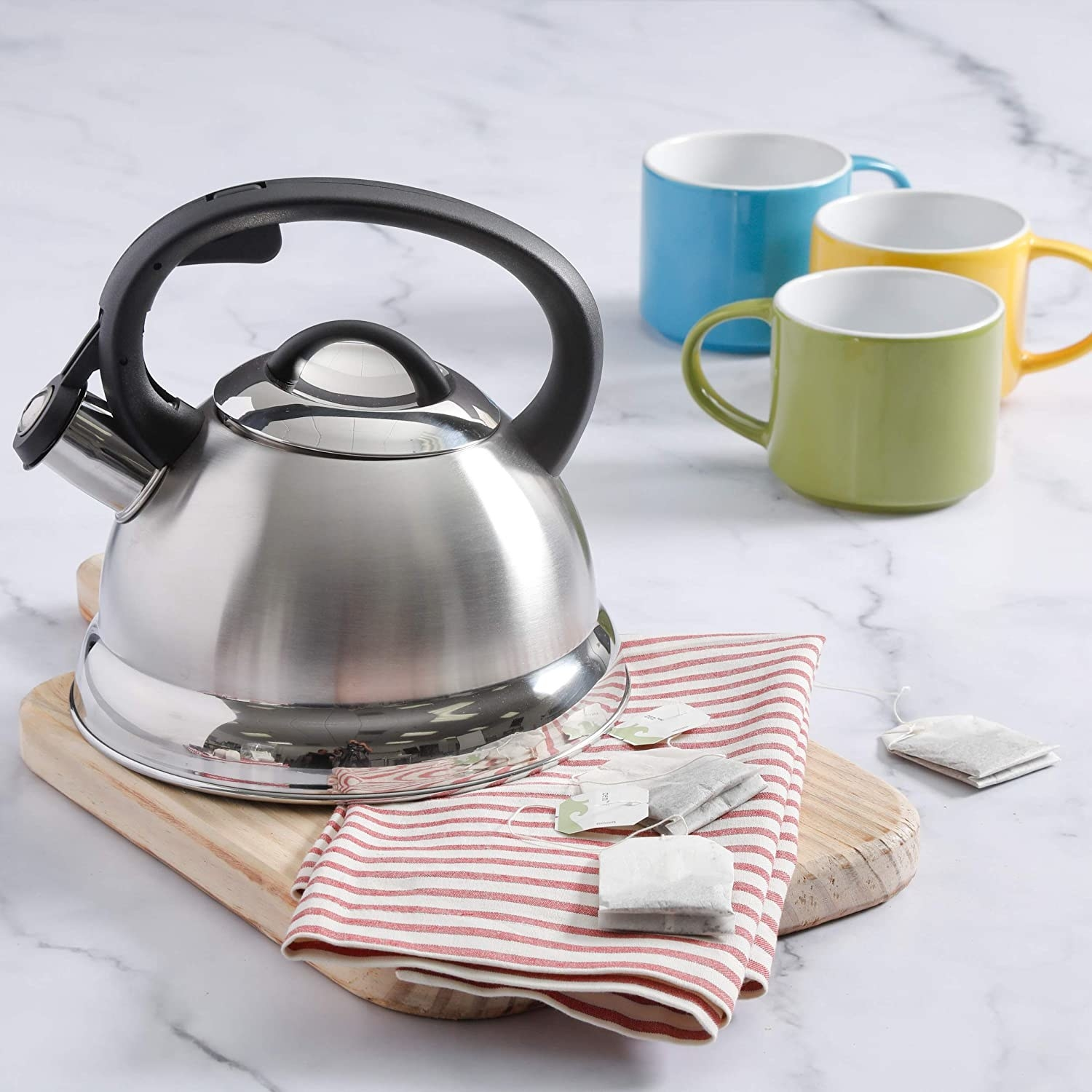 A kettle on a cutting board with tea bags