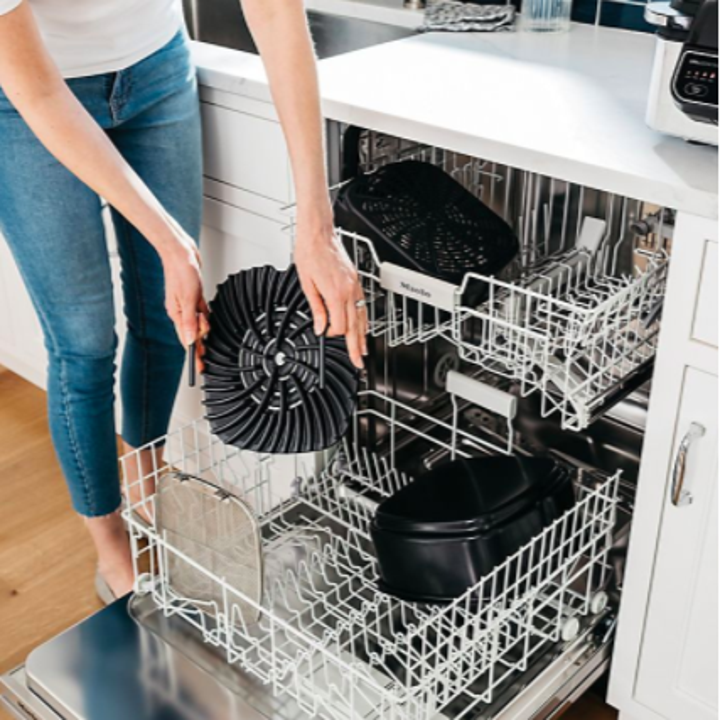 person putting parts into a dishwasher