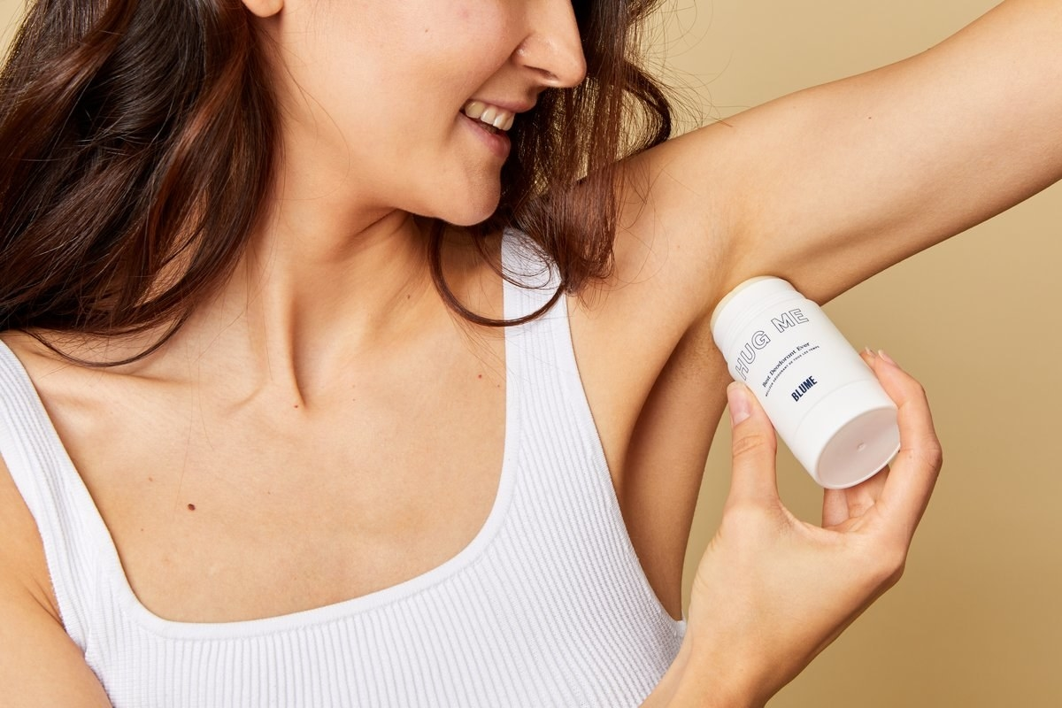 model rubbing the deodorant in her armpits