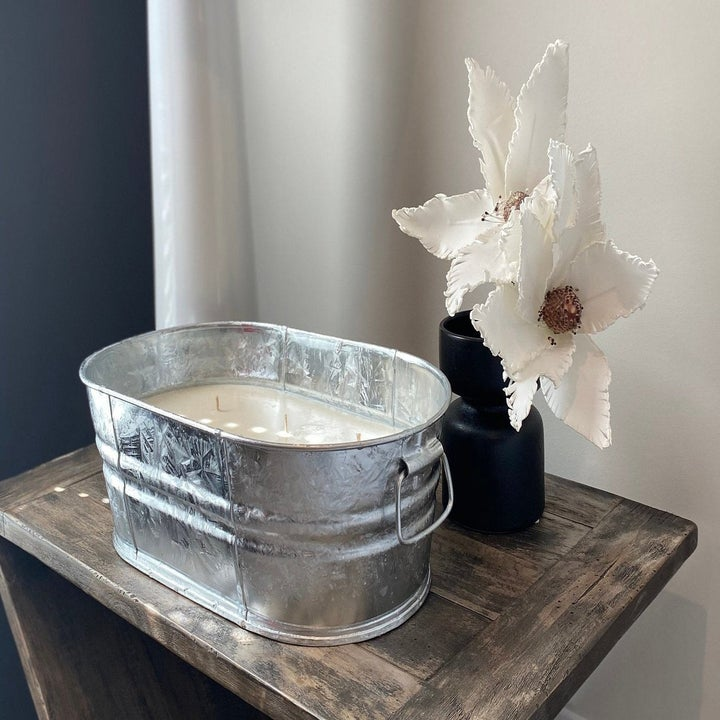 oval round tub filled with a candle. It's about one foot long. Candle wax is white. It's sitting on a table in a home with a flower beside it. This scent is citronella and I can already smell it. What about you?