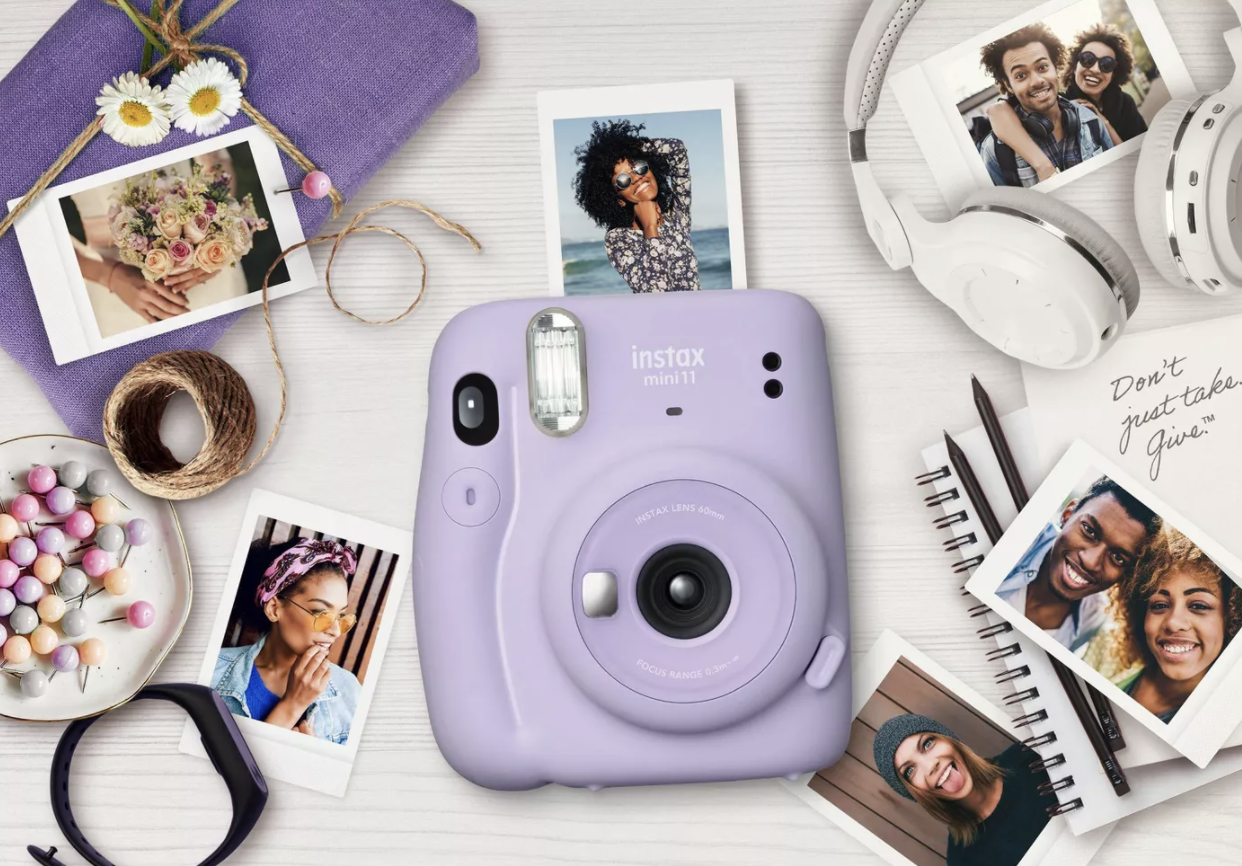 Purple Fujifilm Instax mini camera surrounded by small printed photos