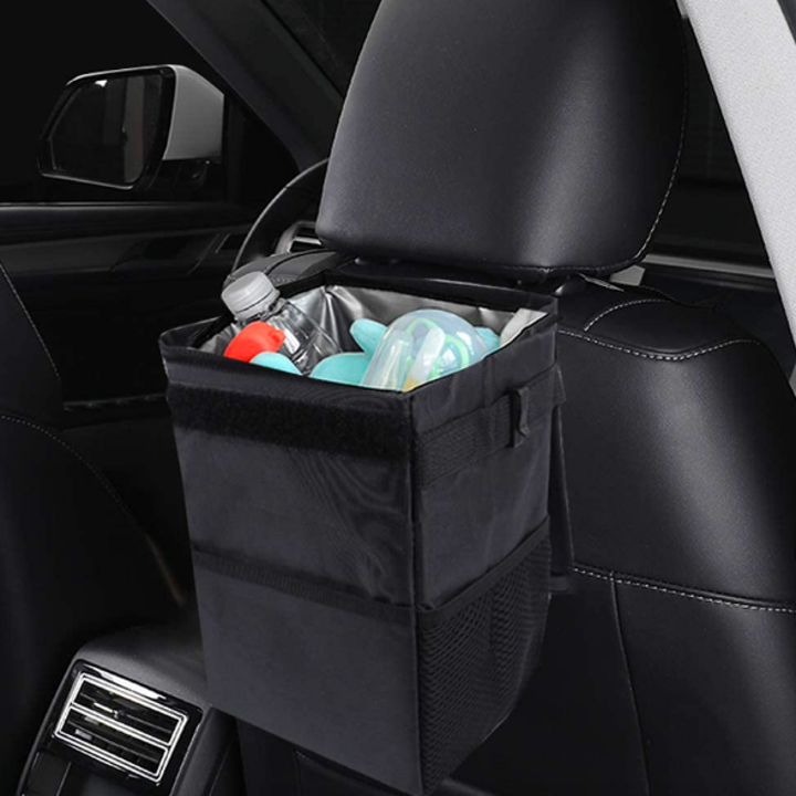 Collapsable rectangular trash can with open lid attached to back of passenger seat