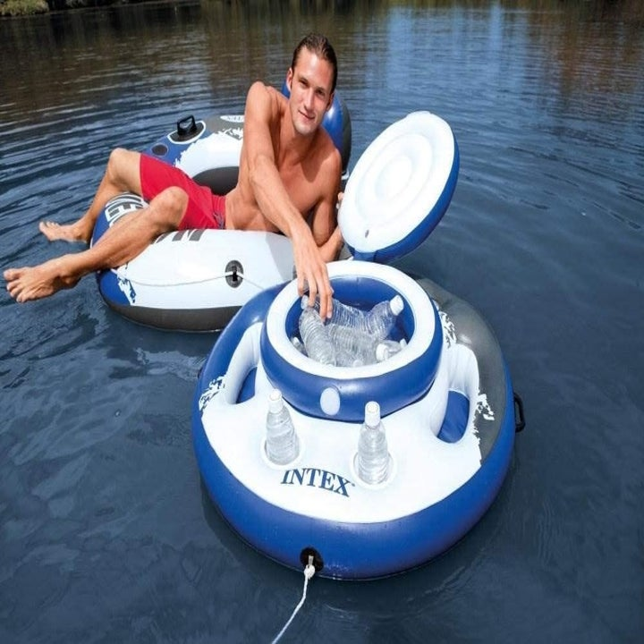 person on a raft with a floating cooler