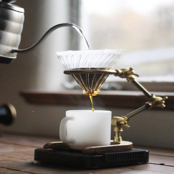 A kettle pouring water over the funnel and dripping coffee into a mug