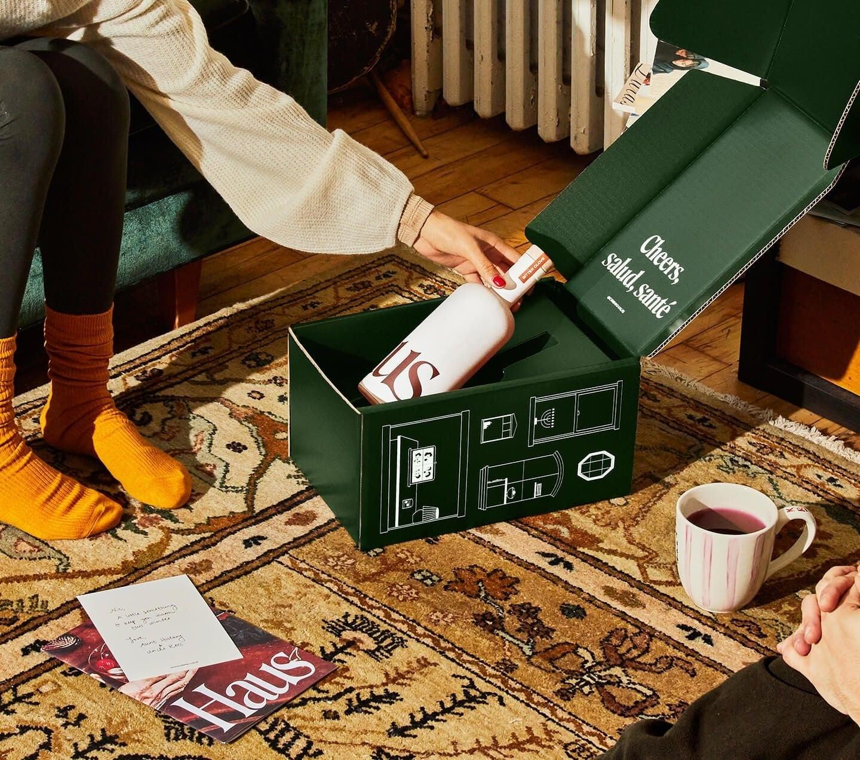 A model opening a gift box encasing a bottle of Haus apéritif