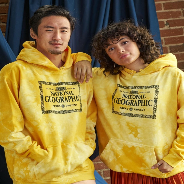 two models wearing yellow tie-dye hooded sweatshirt with National Geographic on it
