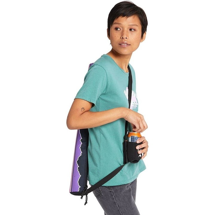 model wearing the vertical insulated cooler on a strap with a coozie on the strap on the front