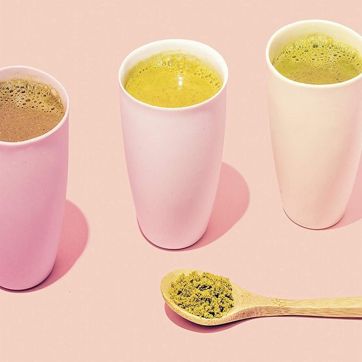 Three cups with various earthy-toned liquids sitting next to the power in a wooden spoon