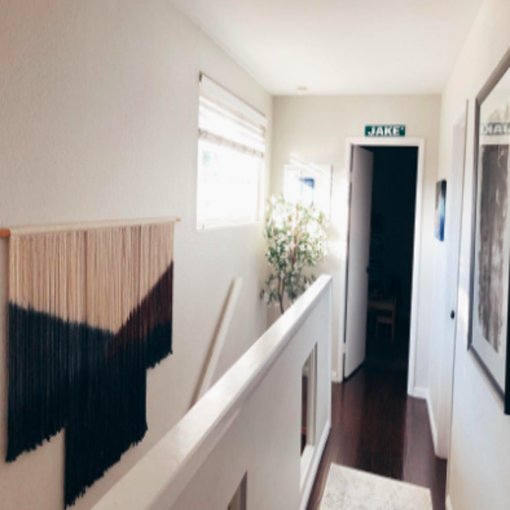 Reviewer with wall hanging on staircase wall