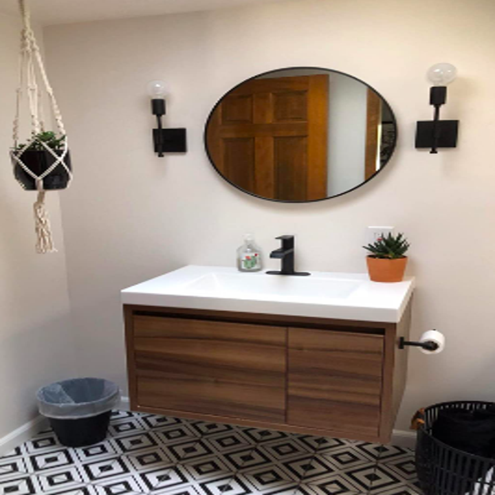 Reviewer's bathroom with sconce lights on either side of large round mirror with black trim